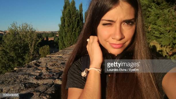 portrait of confident young woman blinking against trees - our lady of lourdes stock pictures, royalty-free photos & images