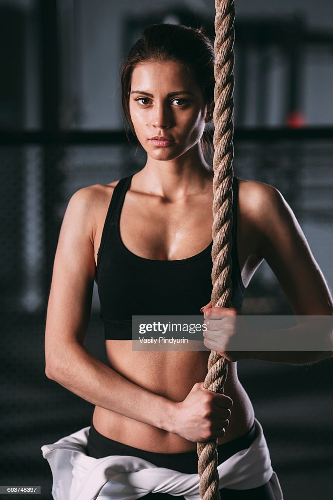 Portrait of confident young woman exercising with rope at gym : Stock Photo
