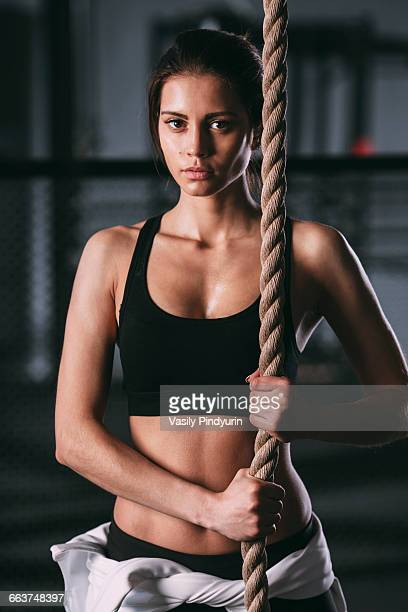 Portrait of confident young woman exercising with rope at gym
