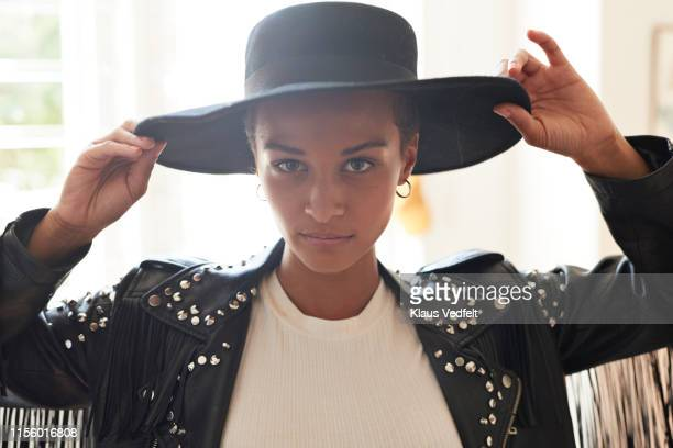 portrait of confident young woman holding black hat - getting dressed stock pictures, royalty-free photos & images