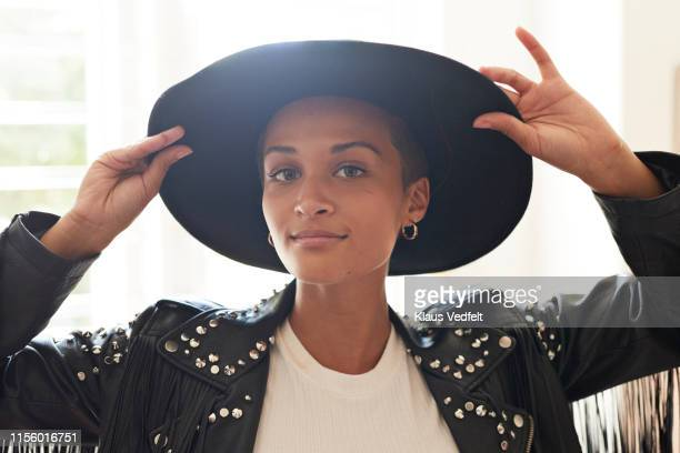 portrait of confident young woman holding hat - black hat stock pictures, royalty-free photos & images