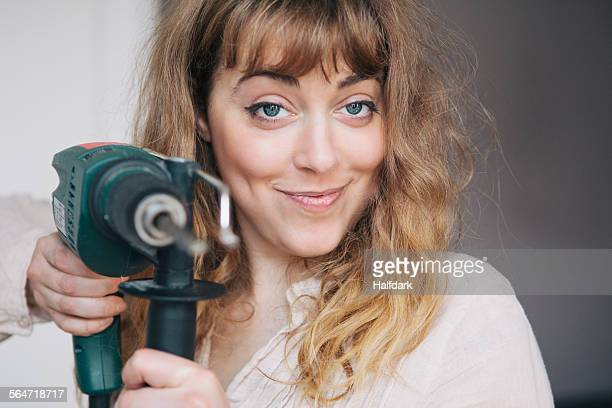 Portrait of confident young woman holding power drill at home