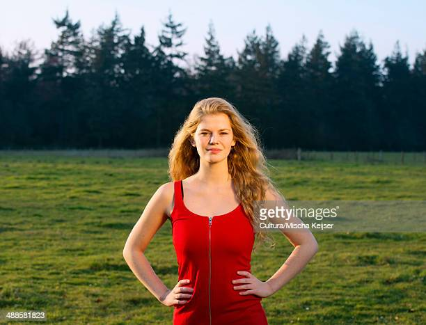 Portrait of confident young woman in field landscape