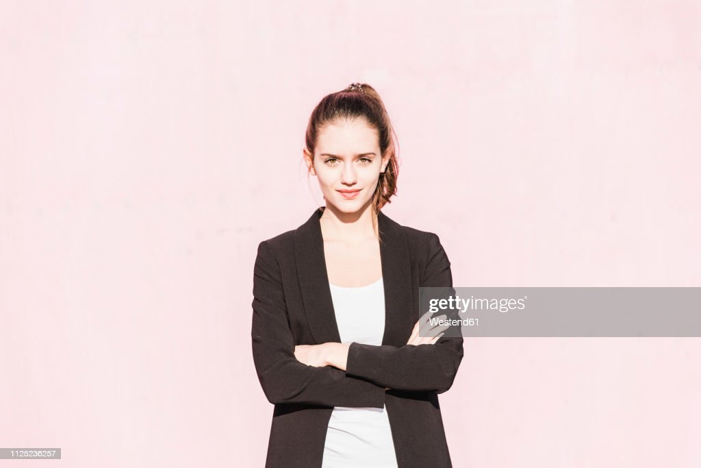 Portrait of confident young woman in front of pink wall : Stock Photo