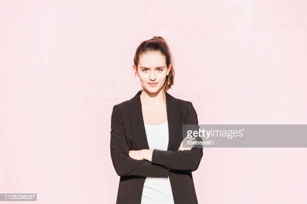 portrait of confident young woman in front of pink wall - fähigkeit stock-fotos und bilder