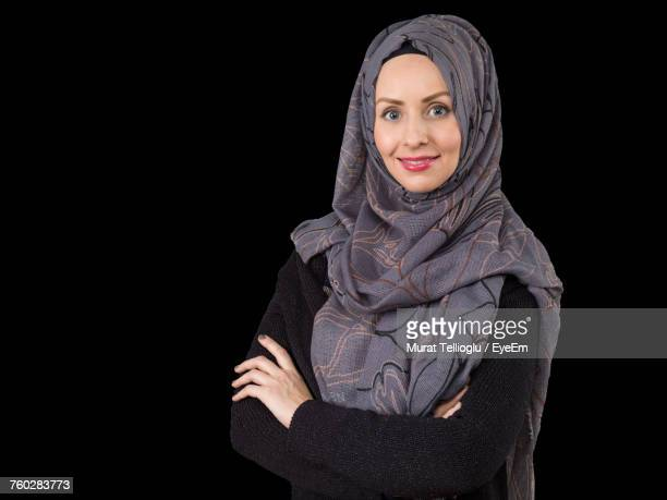Portrait Of Confident Young Woman In Hijab Standing Against Black Background