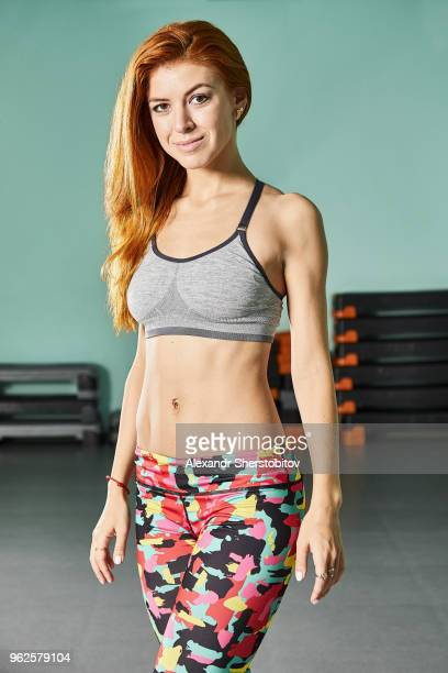 portrait of confident young woman in sports clothing standing at gym - one young woman only stock pictures, royalty-free photos & images