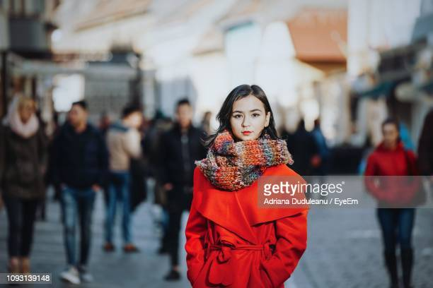 portrait of confident young woman in warm clothing standing on city street - winter coat stock pictures, royalty-free photos & images