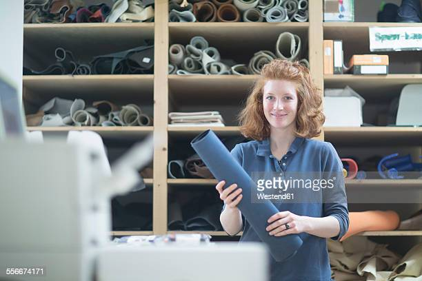Portrait of confident young woman in workshop holding leather roll