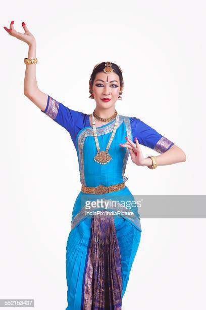 Portrait of confident young woman performing Bharatanatyam over white background
