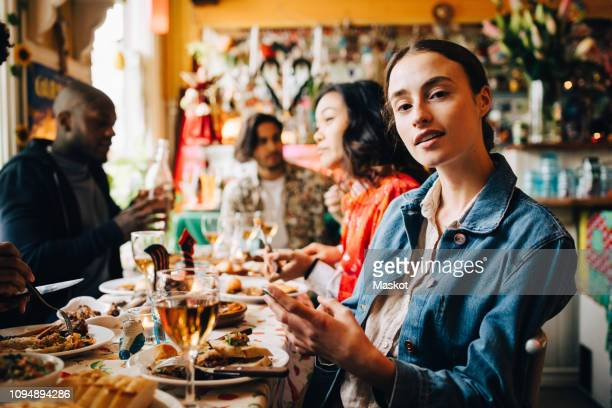 portrait of confident young woman sitting with smart phone against friends at table in restaurant during dinner party - kleine scherptediepte stockfoto's en -beelden