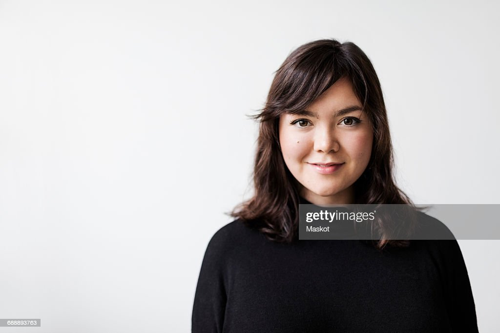 Portrait of confident young woman smiling against white background : Foto de stock