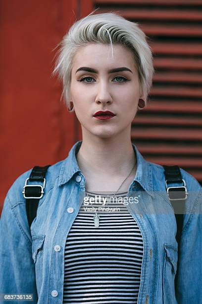 Portrait of confident young woman standing against red wall