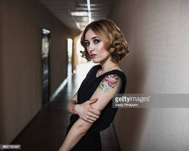 Portrait of confident young woman standing in corridor