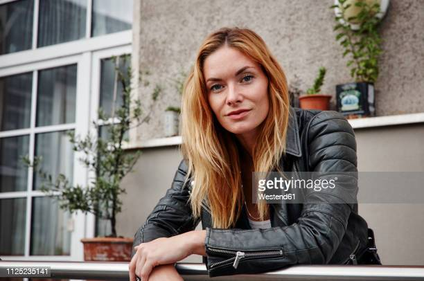 portrait of confident young woman wearing biker jacket leaning on balcony railing - biker jacket stock pictures, royalty-free photos & images