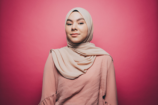Portrait of confident young woman wearing hijab against pink background - gettyimageskorea