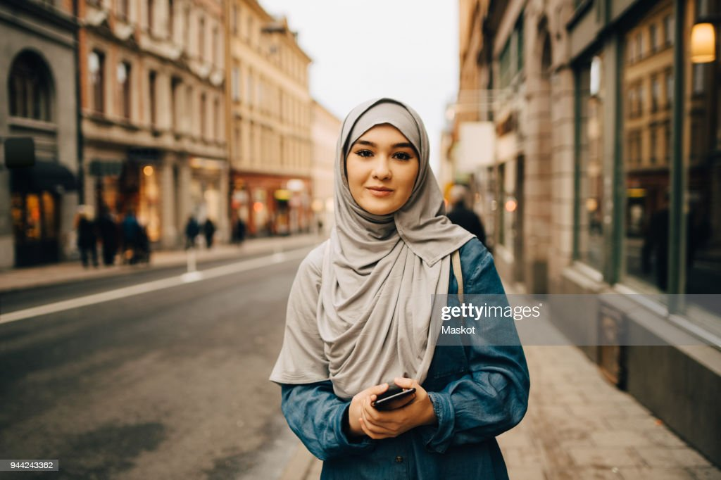 Portrait of confident young woman wearing hijab standing with mobile phone on sidewalk in city : Stock Photo