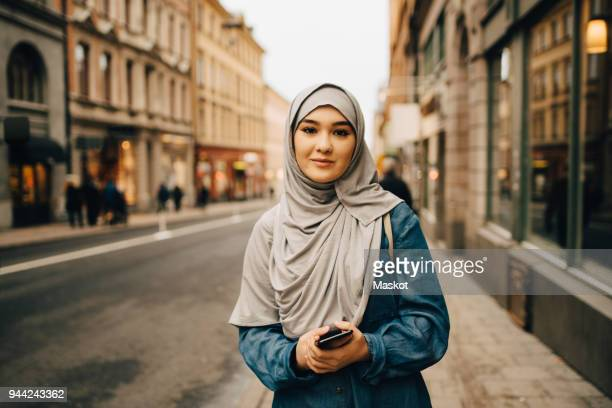 portrait of confident young woman wearing hijab standing with mobile phone on sidewalk in city - islam fotografías e imágenes de stock