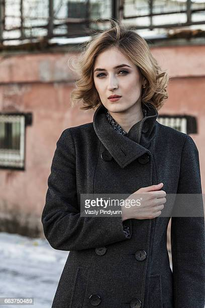 Portrait of confident young woman wearing long coat outdoors