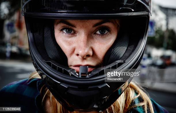 portrait of confident young woman wearing motorcycle helmet - capacete capacete esportivo - fotografias e filmes do acervo