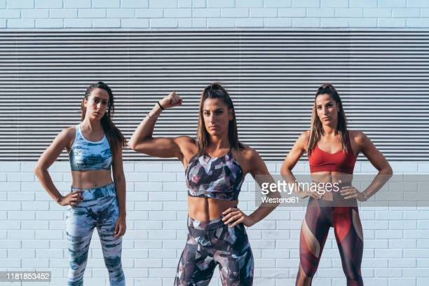 portrait of confident young woman with friends  flexing muscles - hero and not superhero stock pictures, royalty-free photos & images