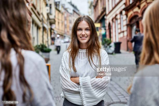 portrait of confident young woman with friends in the city - brown hair stock pictures, royalty-free photos & images