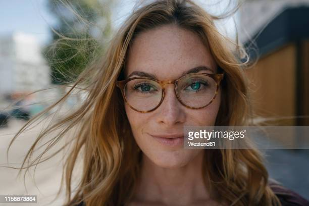 portrait of confident young woman with glasses and windswept hair - windzerzaustes haar stock-fotos und bilder