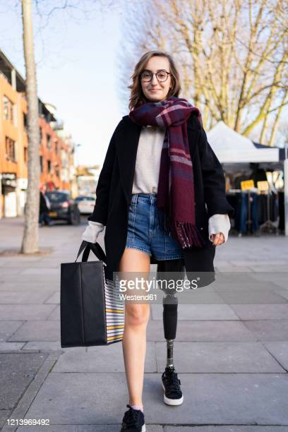 portrait of confident young woman with leg prosthesis walking in the city - persons with disabilities stock pictures, royalty-free photos & images