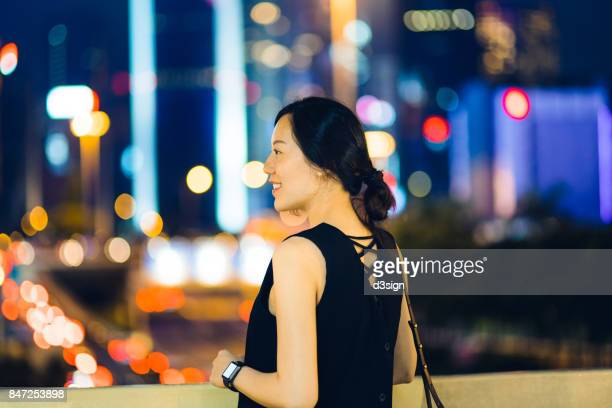 Portrait of confident young woman with smart watch in urban city at night