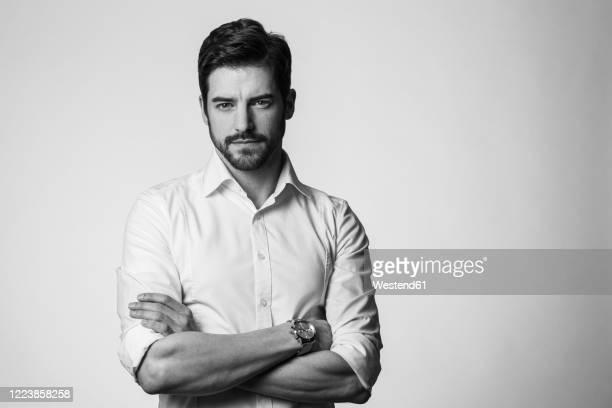 portrait of confindent man, with arms crossed - image en noir et blanc photos et images de collection