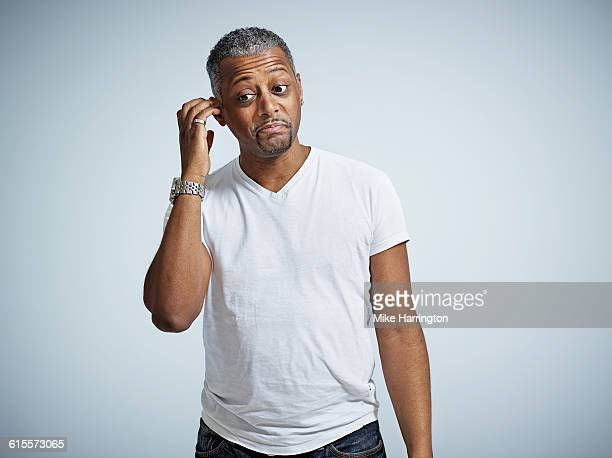 portrait of confused black male - ear stock pictures, royalty-free photos & images