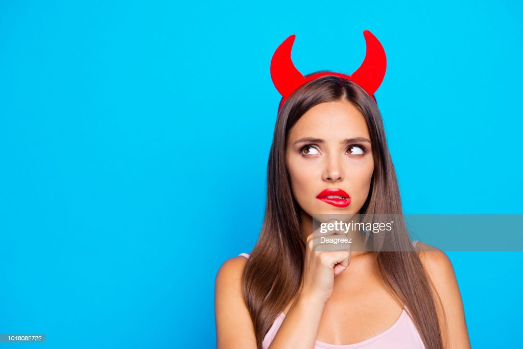 Portrait of confused puzzled unsure straight-haired caucasian girl wearing red horns, biting lip, isolated over bright vivid blue background, red pomade lips : Stock Photo