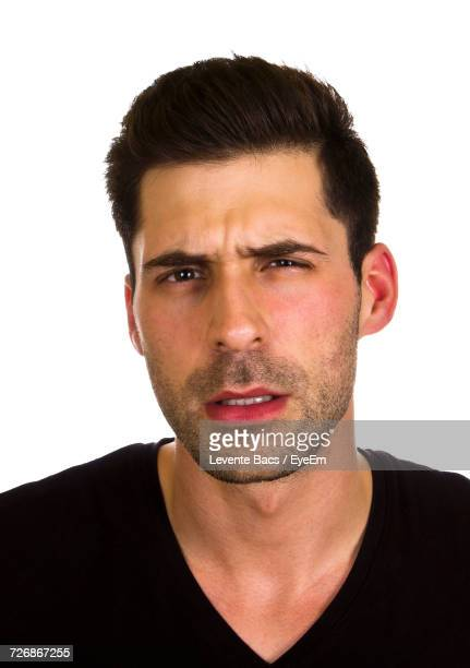 Portrait Of Confused Young Man Standing Against White Background