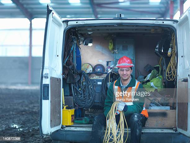 portrait of construction worker holding cables in back of van on building site - electrician stock pictures, royalty-free photos & images