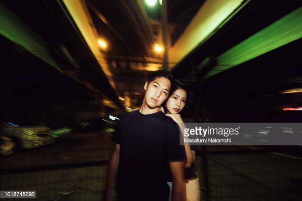 Portrait of contemporary young Japanese couple at night street
