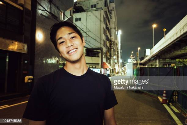 Portrait of contemporary young Japanese man at night street