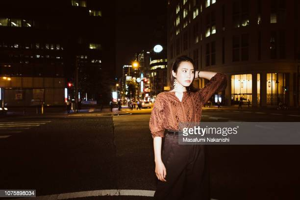 Portrait of contemporary young Japanese woman at night street.