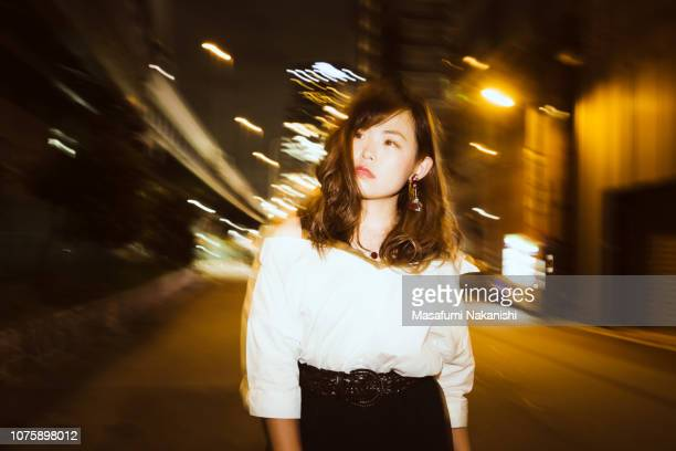 Portrait of contemporary young Japanese woman with city lights at night.