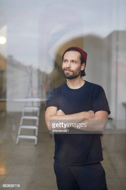 Portrait of content artist in his atelier looking out of window