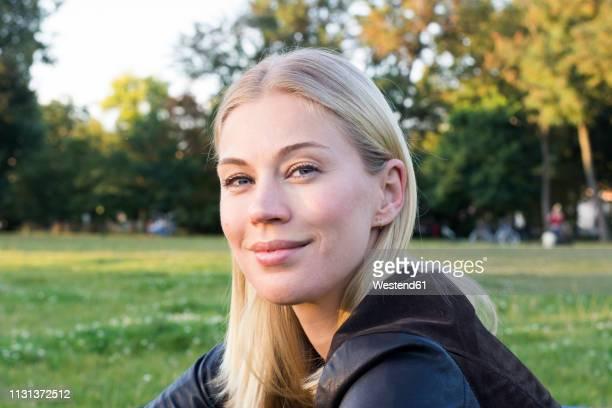 portrait of content blond woman relaxing in a park - endast en kvinna i 30 årsåldern bildbanksfoton och bilder