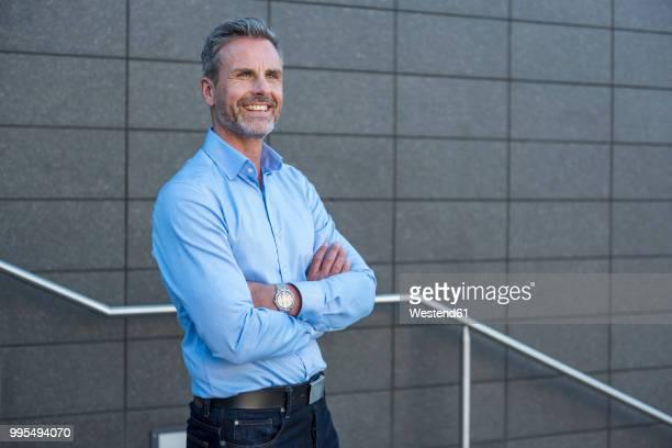 portrait of content businessman wearing light blue shirt - hellblau stock-fotos und bilder