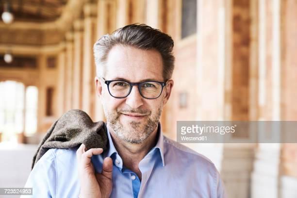 Portrait of content businessman with stubble wearing glasses