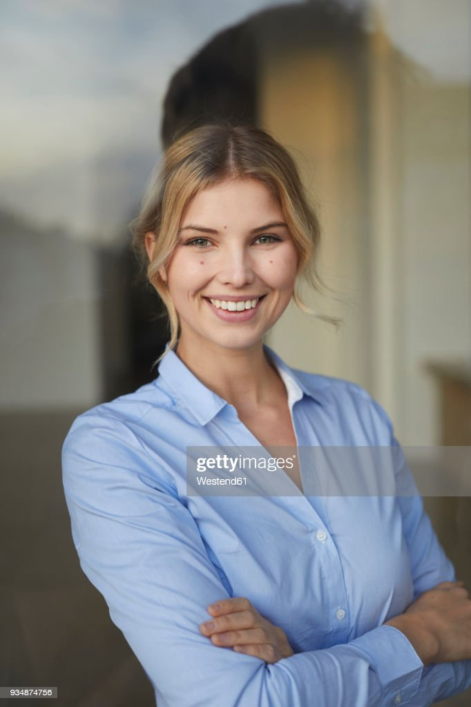 Portrait of content businesswoman behind windowpane : Stock Photo
