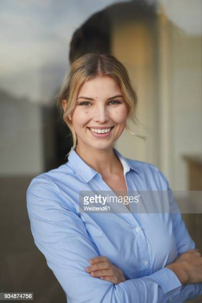 portrait of content businesswoman behind windowpane - bluse stock-fotos und bilder