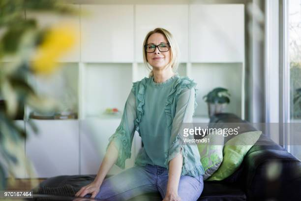 portrait of content businesswoman sitting on couch - orgoglio foto e immagini stock