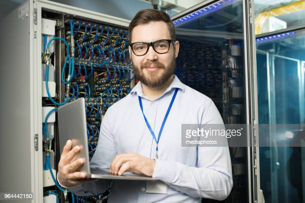 Portrait of content confident bearded highly professional IT engineer with badge on neck using laptop in network server room