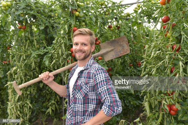 Portrait of content gardener in greenhouse with tomato plants