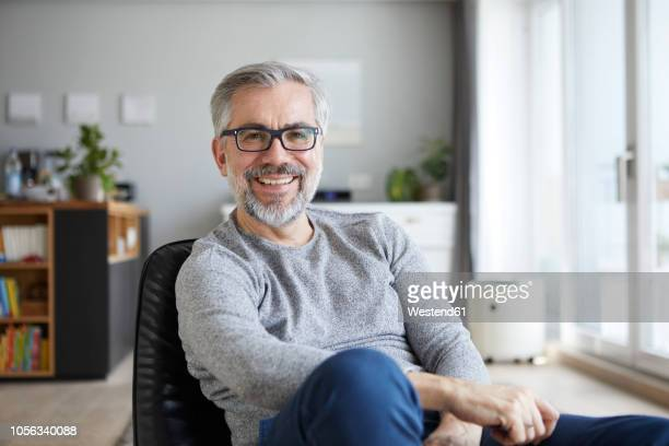 portrait of content mature man in his living room - one mature man only stock pictures, royalty-free photos & images