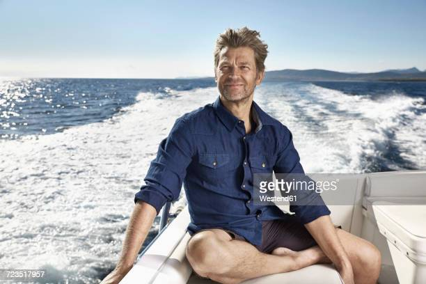 portrait of content mature man on his motor yacht - handsome 50 year old men stock photos and pictures