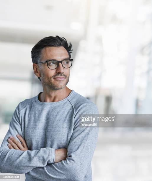 portrait of content mature man with stubble wearing glasses - wegkijken stockfoto's en -beelden